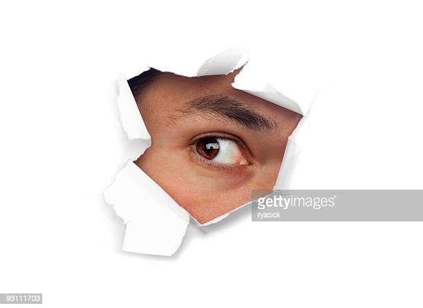 Male Eye Staring Out Of Hole of Ripped White Paper