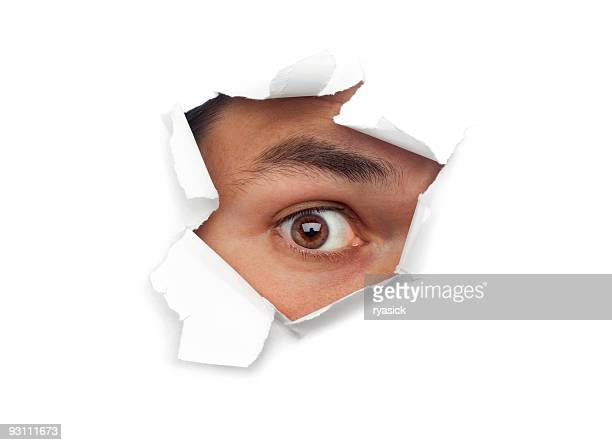 Male Eye Staring Out Through Ripped Paper Hole At Camera