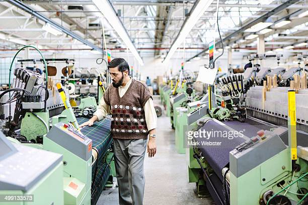 Male factory worker monitoring weaving machine quality in woollen mill