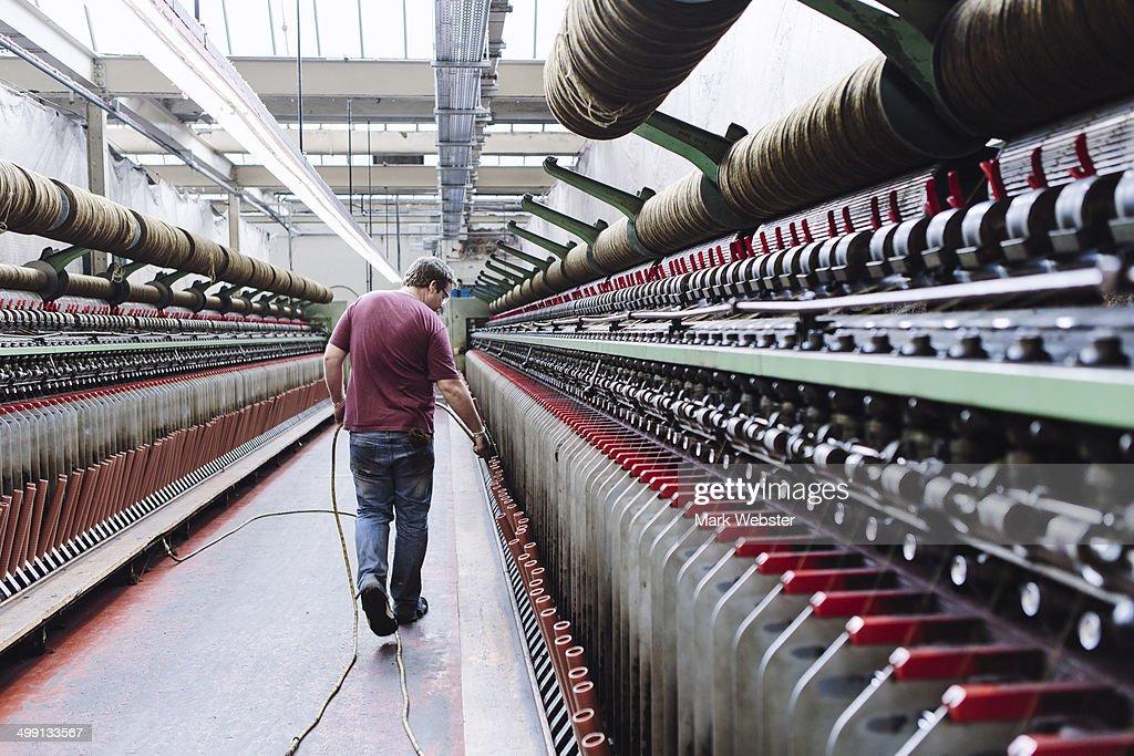 Male factory worker monitoring weaving machines in woollen mill