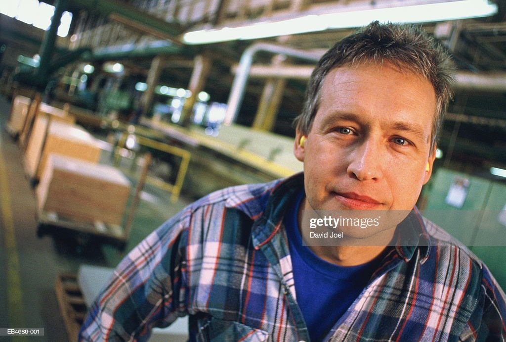 Male factory worker standing in warehouse, portrait : Stock Photo