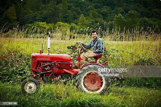 Male farmer driving tractor in field smiling