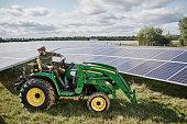 Male farmer using machinery on his solar farm