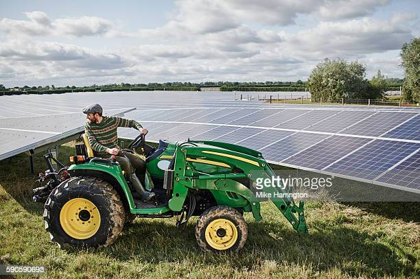 Male farmer using machinery on his solar farm