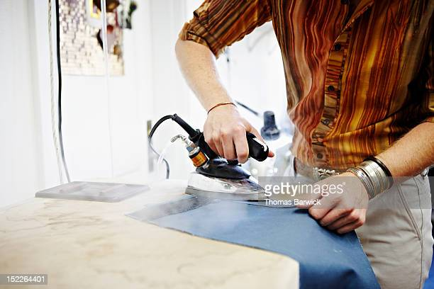 Male fashion designer ironing fabric in studio