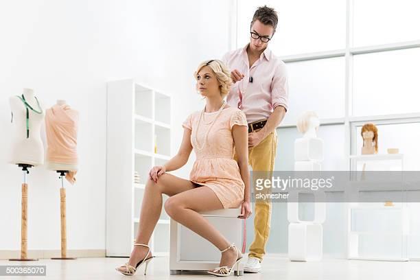 Masculino designer de moda de tomar cliente medições.