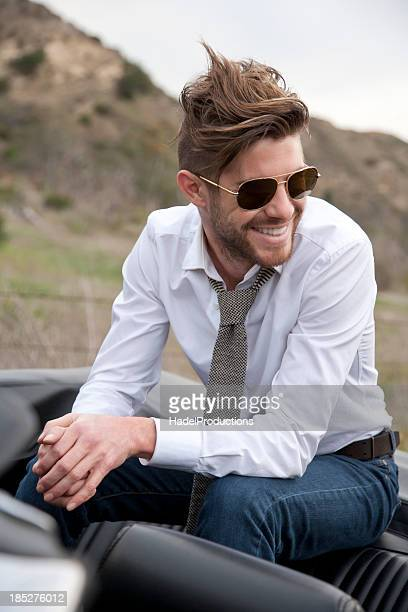 Male Fashion Model sitting in classic sports car