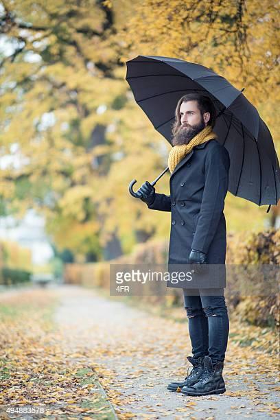 Uomo moda modello con ombrello, colori autunnali