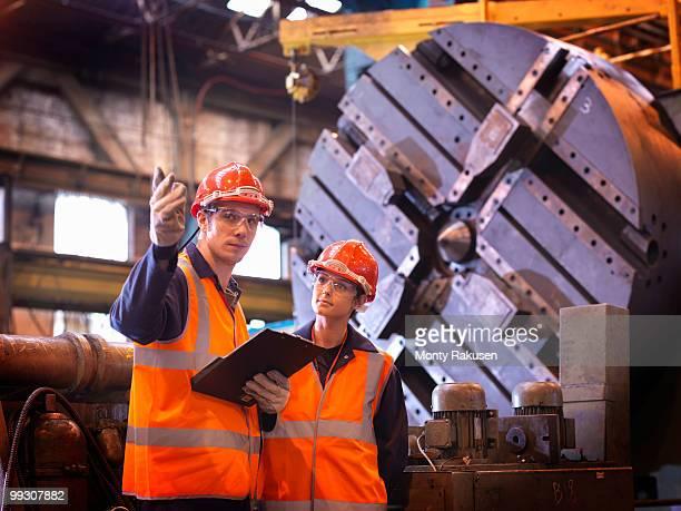 Male & Female Steel Engineers In Factory