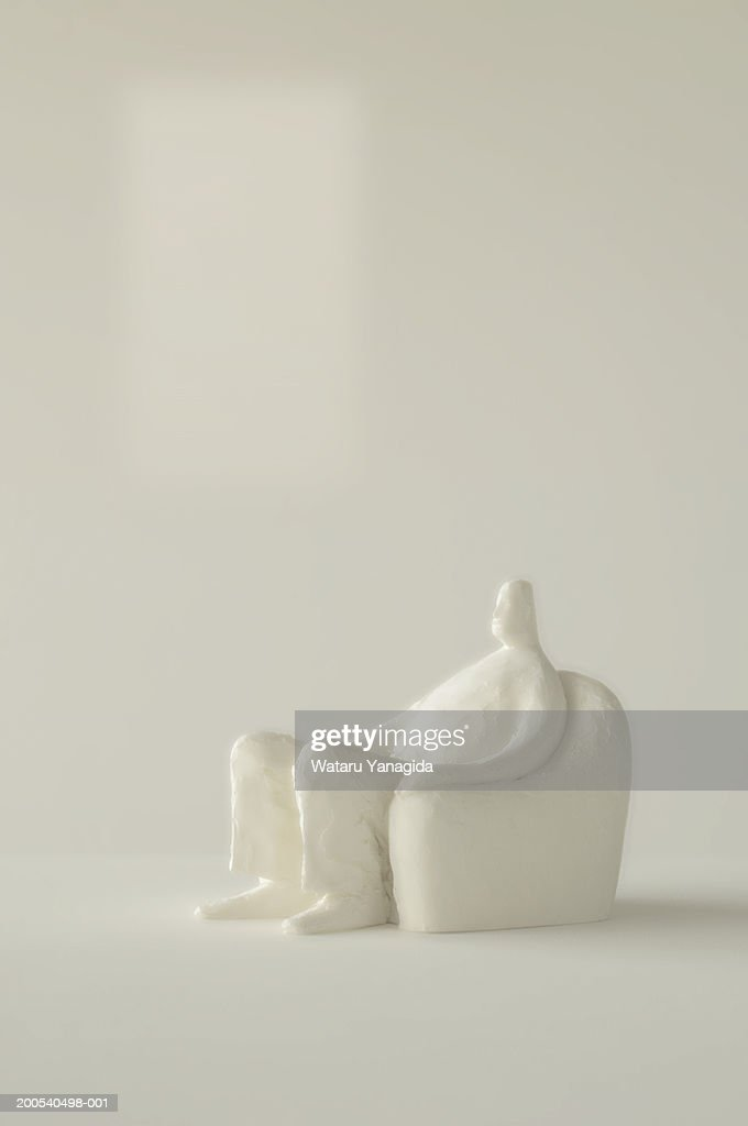 Male figurine sitting on clay armchair, side view
