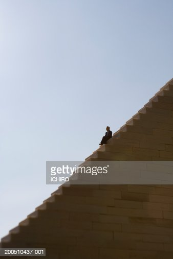 Male figurine sitting on stairway, side view : Stock Photo
