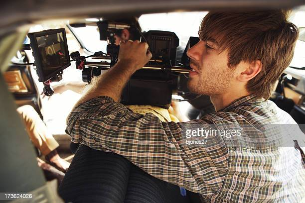 A male filming with a camera for production