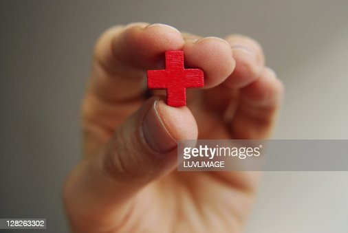 Male fingers hold a little red cross