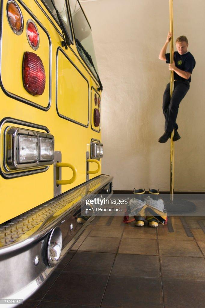 Male firefighter sliding down pole