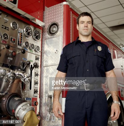 Male firefighter standing beside firetruck, portrait : Stock Photo