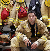 Male firefighter wearing protective clothing, sitting