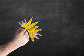 male fist against the black chalkboard. Copy space