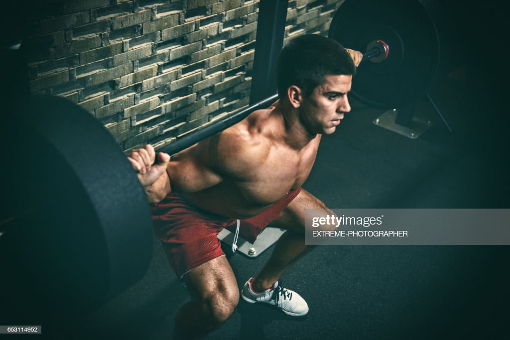 Male fitness athlete performing squats : Stock Photo