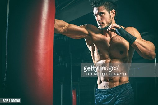 Male fitness athlete punching the bag : Bildbanksbilder