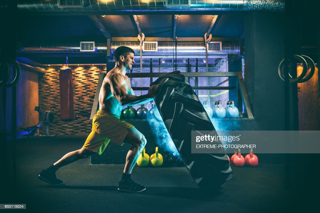 Male fitness athlete rolling the huge tire : Stock Photo