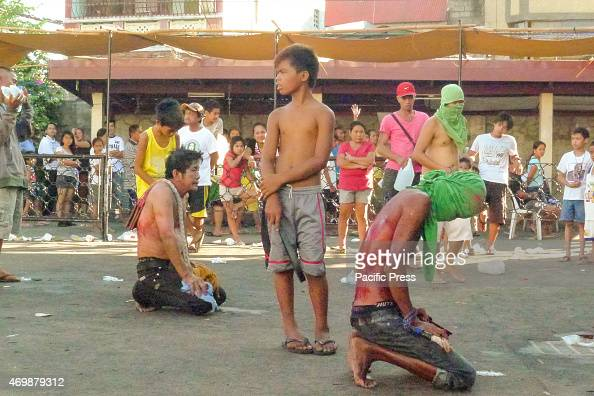 A male flagellant kneeling facing the front of the church while two boys who serves as executioners to the two male flagellants takes a breather