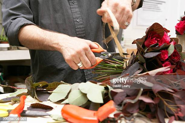Male florist cutting ribbon tied around roses, mid section
