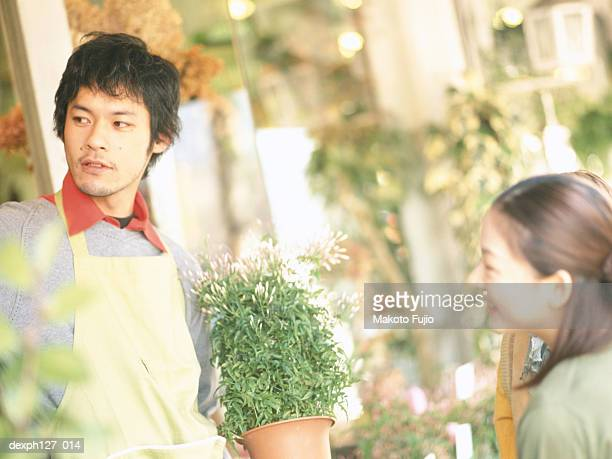 Male florist talking to female customer