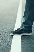 Male foot standing on the white line. Crossing line concept. Male shoe on the asphalt road. Border line concept.