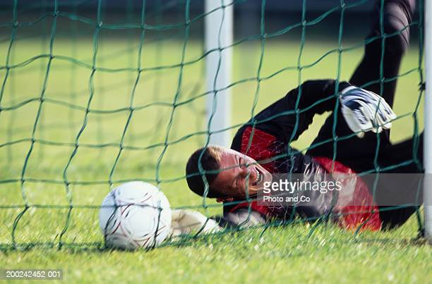 Male football goalie lying on field, reaching for ball