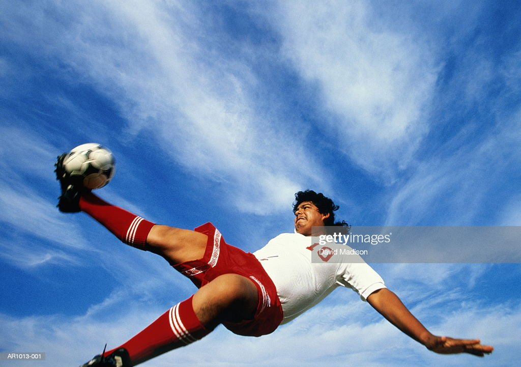 Male football player kicking ball in mid-air, low angle view