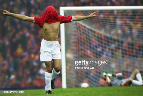 Male football player rejoicing, football shirt over head : Stock Photo