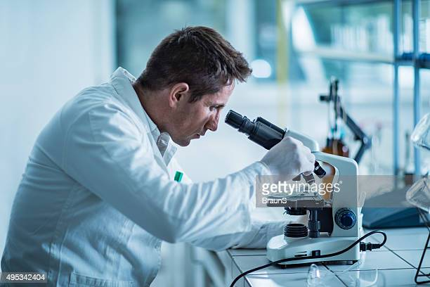 Male forensic scientist examining something through a microscope.