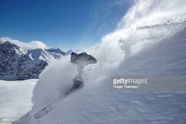 Male freestyle skier skiing down snow powdered mountainside, Zugspitze, Bayern, Germany