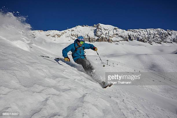 Male freestyle skier skiing down steep mountainside, Zugspitze, Bayern, Germany