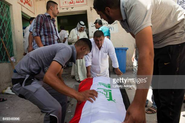 Male friends and relatives of an Iraqi police who was shot in the head while manning a checkpoint in the el Doura neighborhood of Baghdad the night...