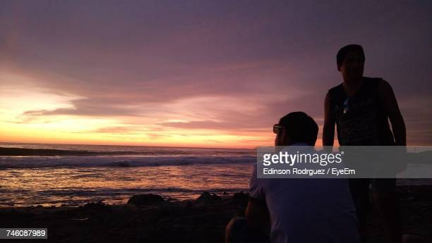 Male Friends At Beach Against Sky During Sunset