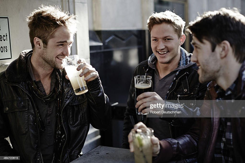 Male friends hanging out and having some drinks. : Stock Photo