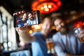 Bearded male couple of friends having a good time in the pub with beer drinks as one of them is holding mobile phone and capturing a selfie image.