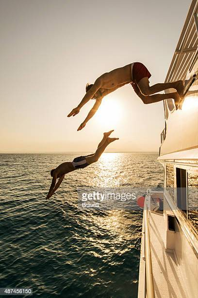Male friends jumping into the sea from a yacht.