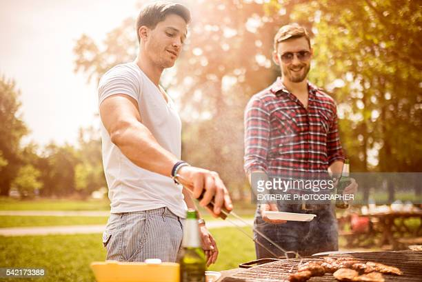 Male friends on a barbecue picnic