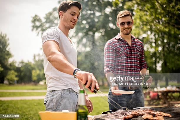 Amigos do sexo masculino em um Churrasco Piquenique