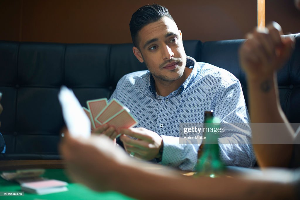 Male friends playing card game at pub card table