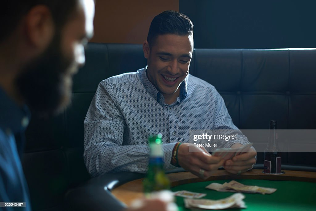 Male friends playing card game for cash at pub card table