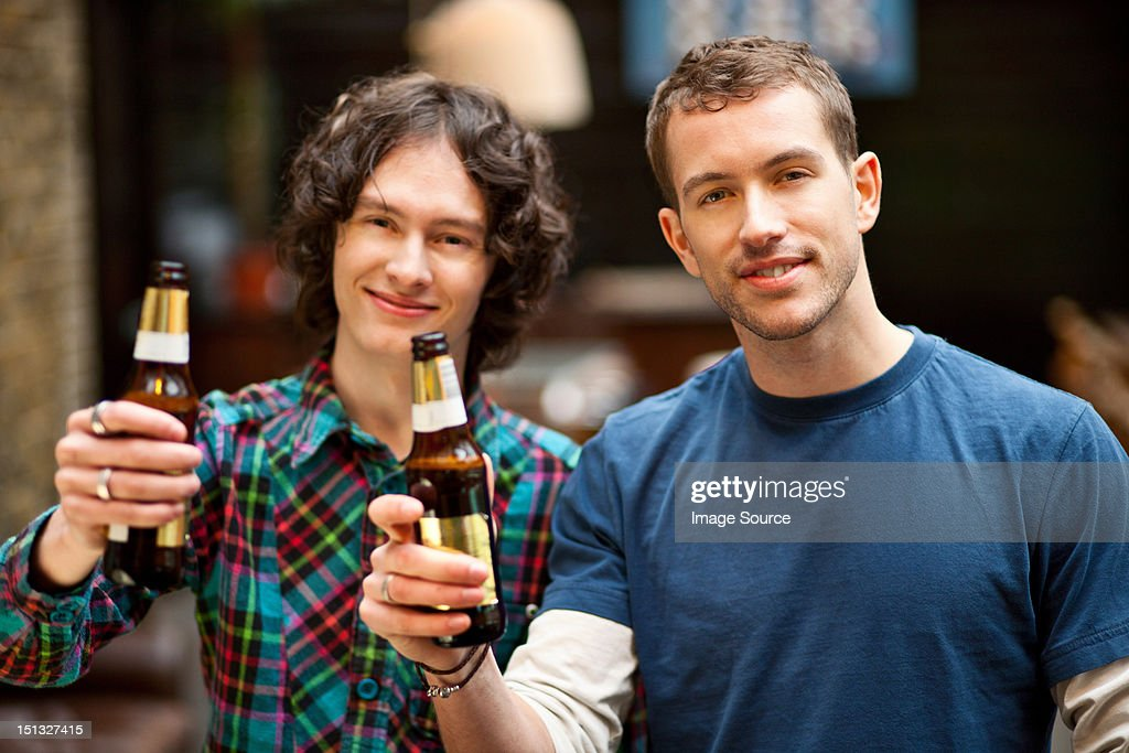 Male friends posing with beer bottles : Stock Photo
