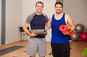 Portrait of a couple of guys carrying exercise mats and smiling in a yoga studio