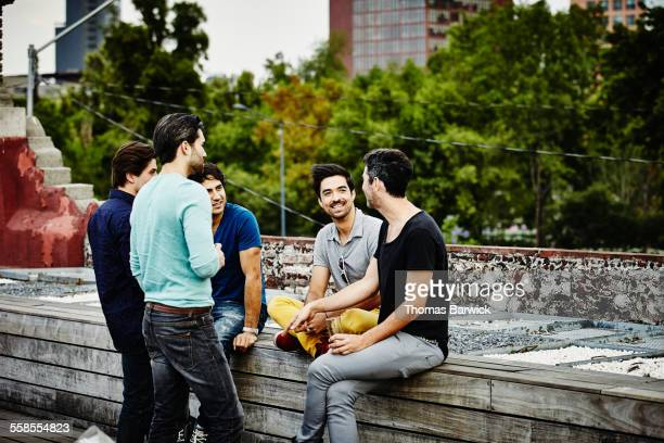 Male friends sharing drinks together on deck
