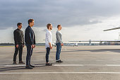 Four young men are waiting for take-off. They are looking at plane with anticipation