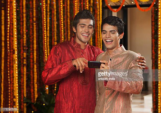 Male friends text messaging on a mobile phone on Diwali