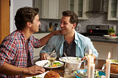 Male gay couple having a romantic dinner in their kitchen