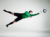 Male goalie diving in mid air to stop soccer ball